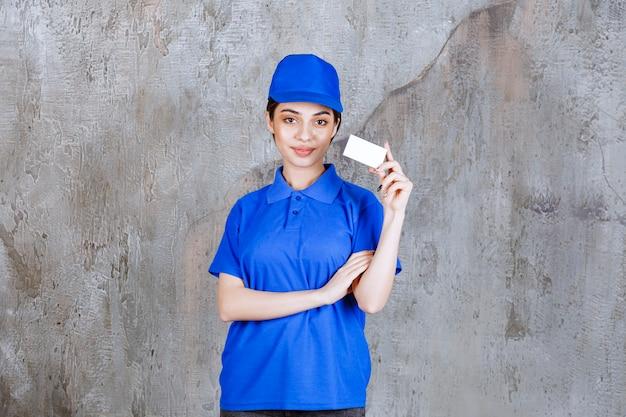 Weiblicher dienstleister in der blauen uniform, die ihre visitenkarte präsentiert.