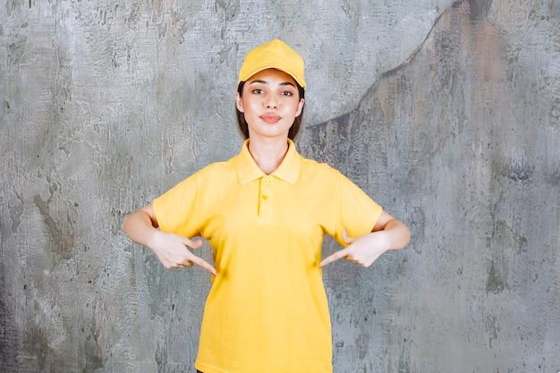 Weiblicher dienstleister in der gelben uniform, die auf betonwand steht und unten zeigt.