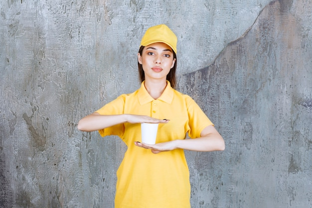 Weiblicher dienstleister in der gelben uniform, die einen plastikbecher hält.