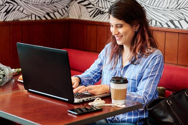 Weiblicher digitaler nomade, der im café arbeitet
