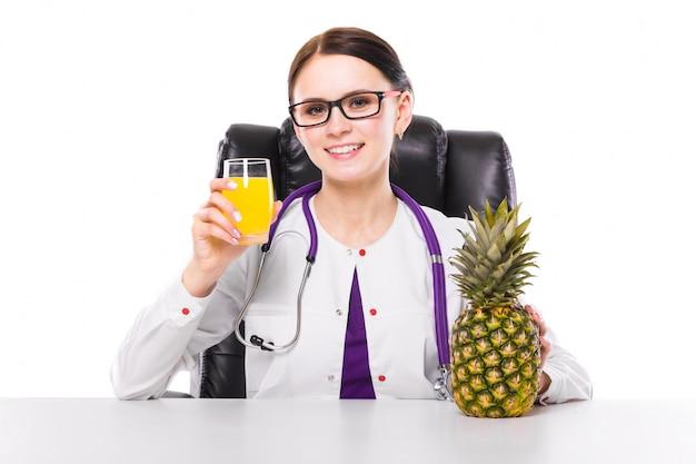 Weiblicher ernährungswissenschaftler, der an ihrem arbeitsplatz zeigt und glas frischen saft der ananas anbietet sitzt