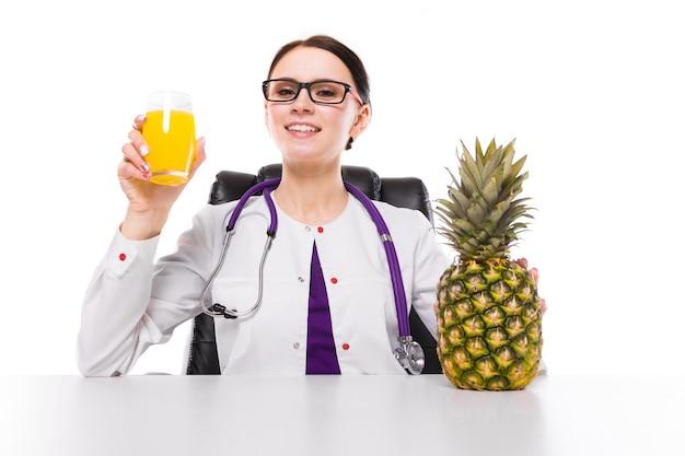 Weiblicher ernährungswissenschaftler, der an ihrem arbeitsplatz zeigt und glas frischen saft der ananas hält ananas in ihrer hand auf weißem hintergrund anbietet sitzt
