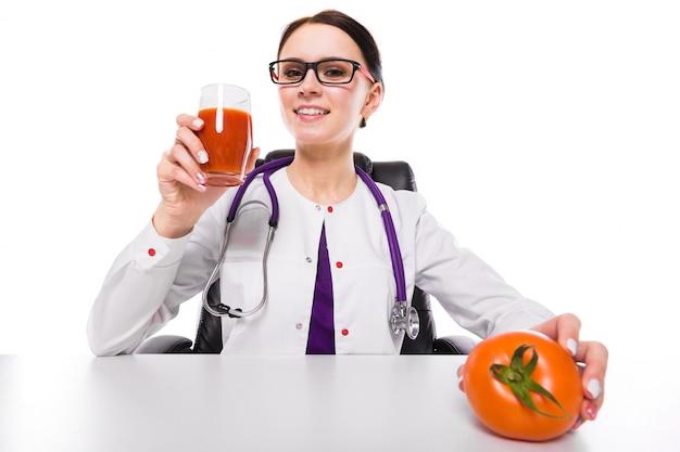 Weiblicher ernährungswissenschaftler, der an ihrem arbeitsplatz zeigt und glas frischen saft der tomate hält tomate in ihrer hand anbietet sitzt