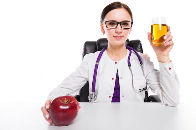Weiblicher ernährungswissenschaftler, der an ihrem arbeitsplatz zeigt und glas frischen saft des apfels hält apfel in ihrer hand auf weiß anbietet