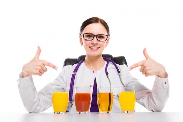 Weiblicher ernährungswissenschaftler, der an ihrem arbeitsplatz zeigt und glas orange apfeltomatensaft der ananas anbietet sitzt