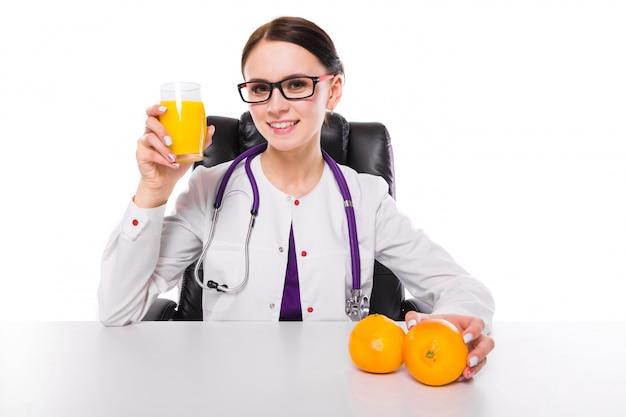 Weiblicher ernährungswissenschaftler, der an ihrem arbeitsplatz zeigt und glas orange frischen saft hält orange in ihrer hand anbietet sitzt