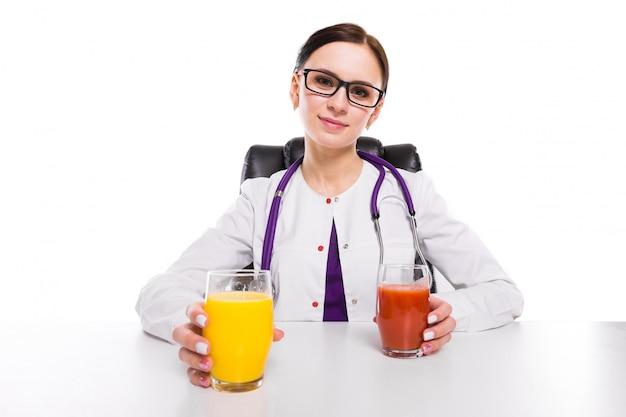 Weiblicher ernährungswissenschaftler, der an ihrem arbeitsplatz zeigt und glas tomate und orange frischen saft auf weißem hintergrund anbietet sitzt