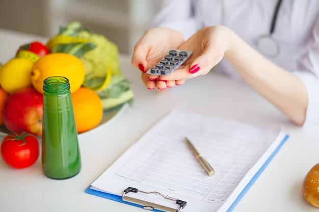 Weiblicher ernährungswissenschaftler holding blisters of pills