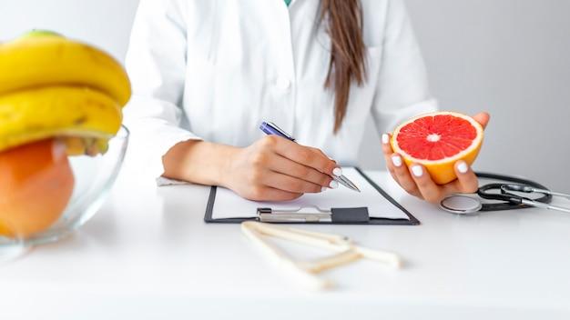 Weiblicher ernährungswissenschaftler mit den früchten, die an ihrem schreibtisch arbeiten.
