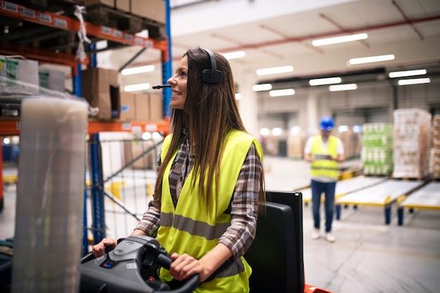Weiblicher fabrikarbeiter, der gabelstapler im lagerbereich fährt, während ihr mitarbeiter notizen im hintergrund macht