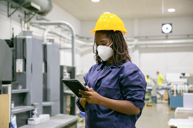 Weiblicher fabrikarbeiter in der maske, die tablette hält