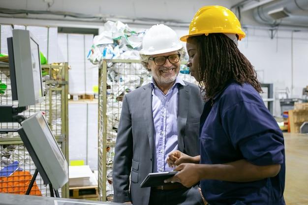 Weiblicher fabrikarbeiter und männlicher ingenieur, der auf werksboden spricht, während frau mit tablettenbetriebsmaschine