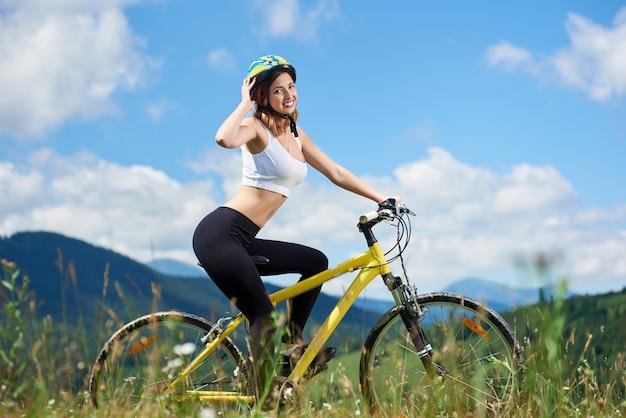 Weiblicher fahrer, der auf gelbem mountainbike auf einem gras radelt und sommertag genießt