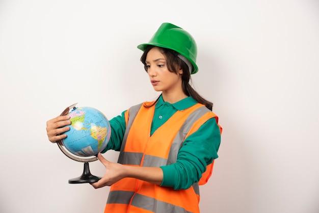 Weiblicher feuerwehrmann, der globus mit ernstem ausdruck auf weißem hintergrund betrachtet.