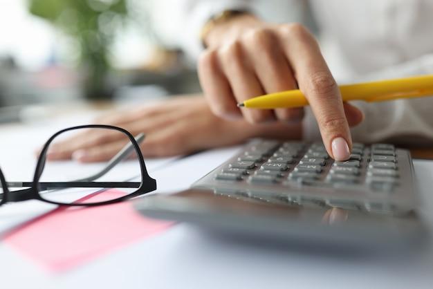 Weiblicher finger auf einem taschenrechner in der nähe von dokumenten