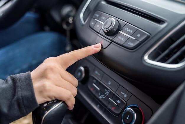 Weiblicher finger, der auf not-aus-knopfnahaufnahme zeigt