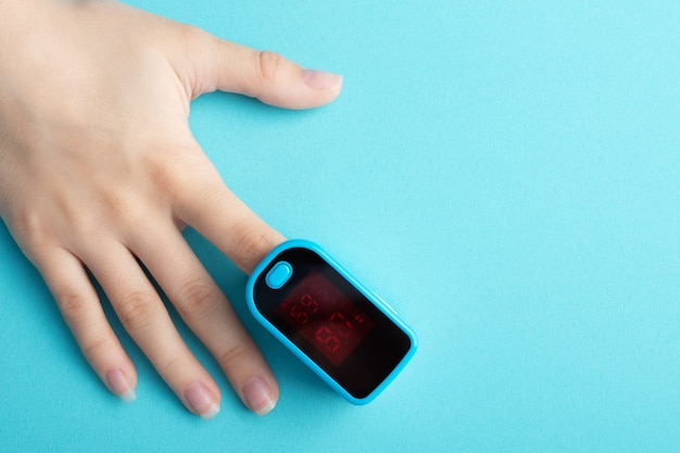 Weiblicher finger in einem pulsoximeter auf blau