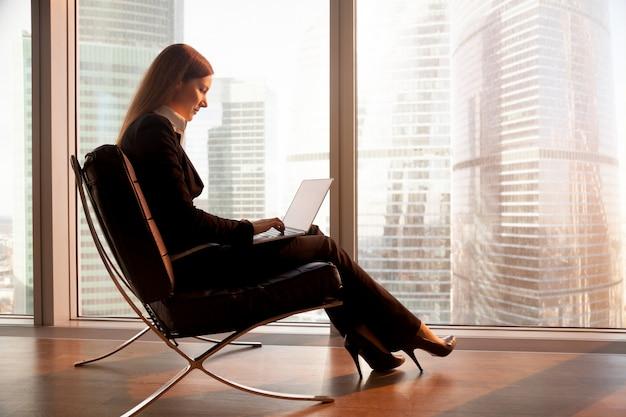 Weiblicher firmenführer, der an laptop im hotel arbeitet