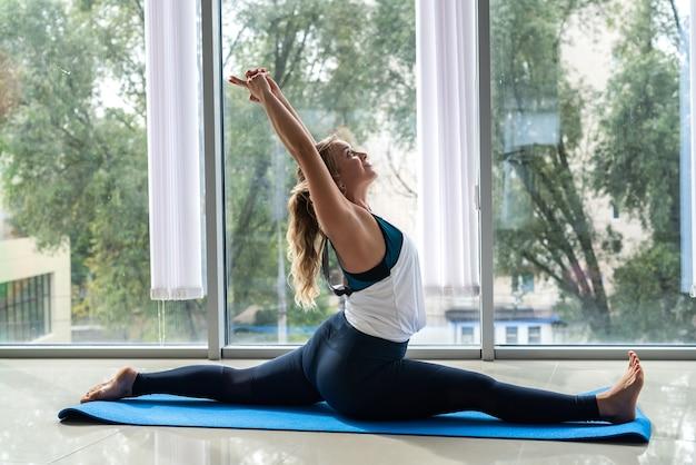 Weiblicher fitnesstrainer, der yogatherapie-pose von rückenschmerzen macht. gesundheitskonzept