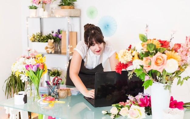 Weiblicher florist, der an laptop mit blumen auf schreibtisch arbeitet