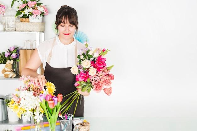 Weiblicher florist, der blumen im blumenshop sortiert