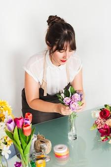 Weiblicher florist, der blumen in vase einsetzt