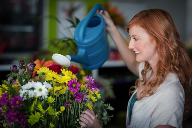 Weiblicher florist, der blumen wässert