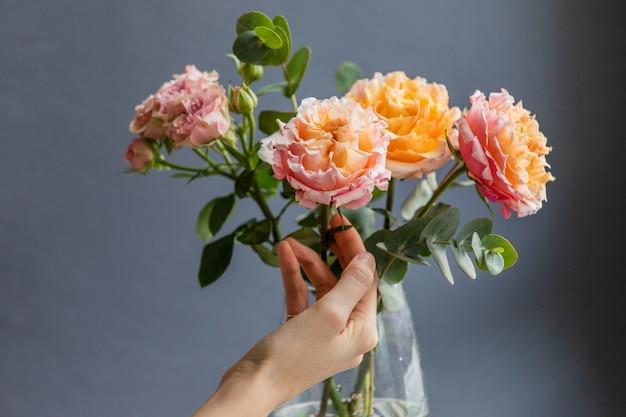 Weiblicher florist, der blumenanordnung für pfingstrosen- und strauchrosen und eukalyptuszweige trifft.