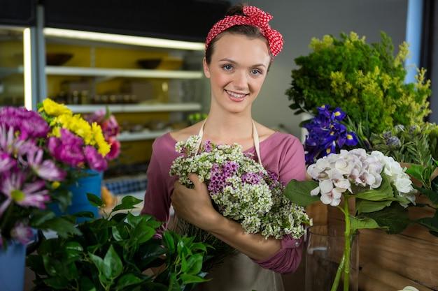 Weiblicher florist, der blumenstrauß im blumenladen hält