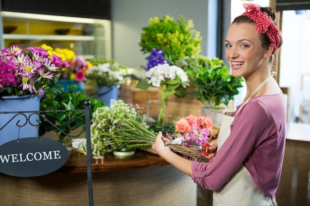 Weiblicher florist, der blumenstrauß im blumenladen vorbereitet
