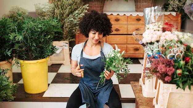 Weiblicher florist, der blumenstrauß im shop hält
