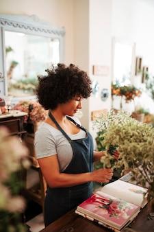 Weiblicher florist, der bündel der blumenanlage mit fotoalbum auf schreibtisch hält
