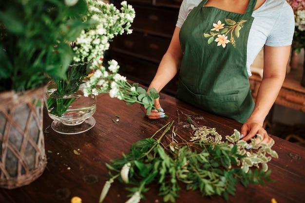 Weiblicher florist, der bündel frische weiße blumen über hölzernem schreibtisch hält