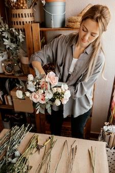 Weiblicher florist, der ein schönes blumenarrangement macht