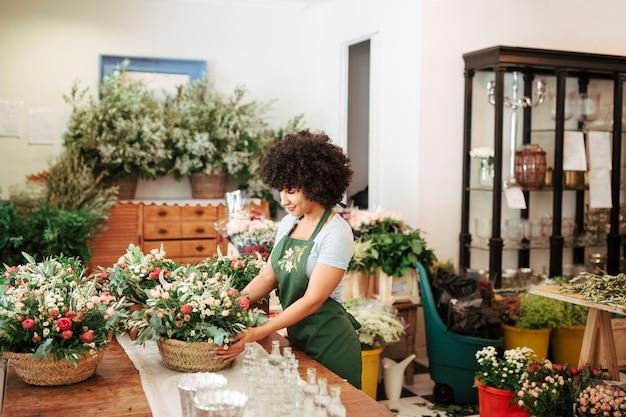 Weiblicher florist, der korb von blumen im blumenshop vereinbart