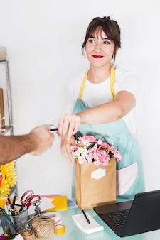 Weiblicher florist, der kreditkarte vom kunden nimmt