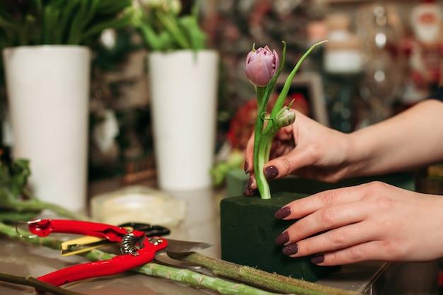Weiblicher florist, der mit blumen arbeitet