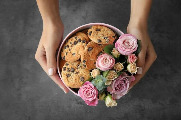 Weiblicher florist, der schachtel mit schönen blumen und keksen, nahaufnahme vorbereitet