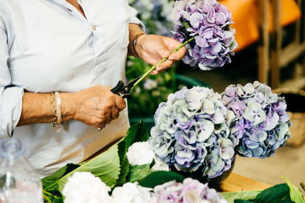 Weiblicher florist, der schöne blumenstrauße bei der stellung am blumenladen macht