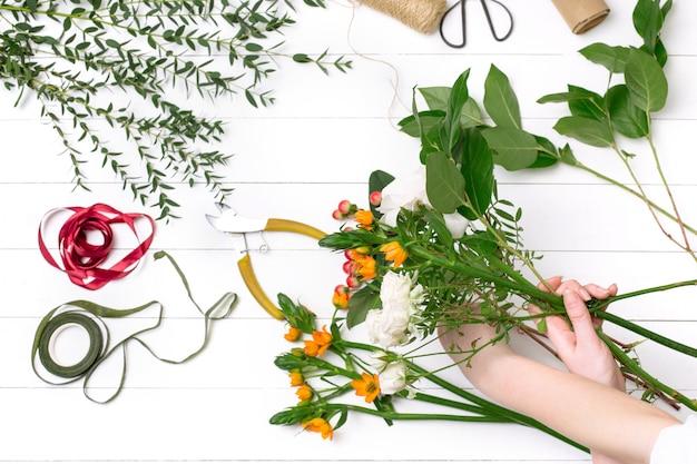 Weiblicher florist, der schönen blumenstrauß am blumenladen macht