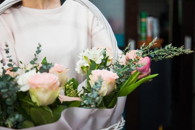 Weiblicher florist designer, der blumen sammelt, um einen blumenstrauß im weißen korb zu machen. blumenladen, der geschenke für urlaub oder dekoration vorbereitet. blumenlieferkonzept.