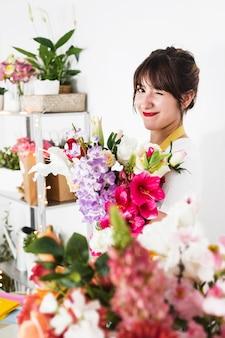 Weiblicher florist mit dem blumenstrauß, der im blumenshop blinzelt