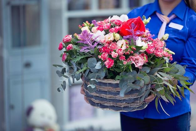 Weiblicher florist mit einem blumenstrauß innerhalb des korbes
