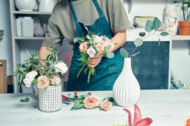 Weiblicher florist unkonzentriert im blumenladen, der schönen künstlichen blumenstrauß macht. ein lehrer für floristik in meisterklassen oder kursen. professionelles, florales dekorationsstudio. kopieren sie platz für design