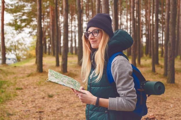Weiblicher forscher mit der karte im freien im wald im herbst