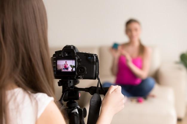 Weiblicher fotograf, der foto des mädchens auf sofa macht.