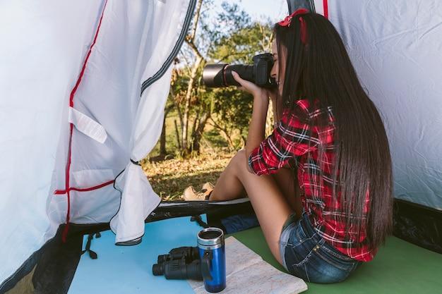 Weiblicher fotograf, der foto mit kamera im zelt macht