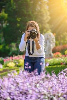Weiblicher fotograf, der fotos von blumen macht