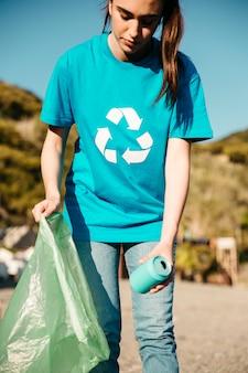 Weiblicher freiwilliger, der abfall am strand sammelt