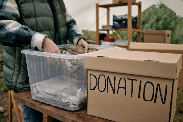 Weiblicher freiwilliger, der gefaltete kleidung in den behälter legt